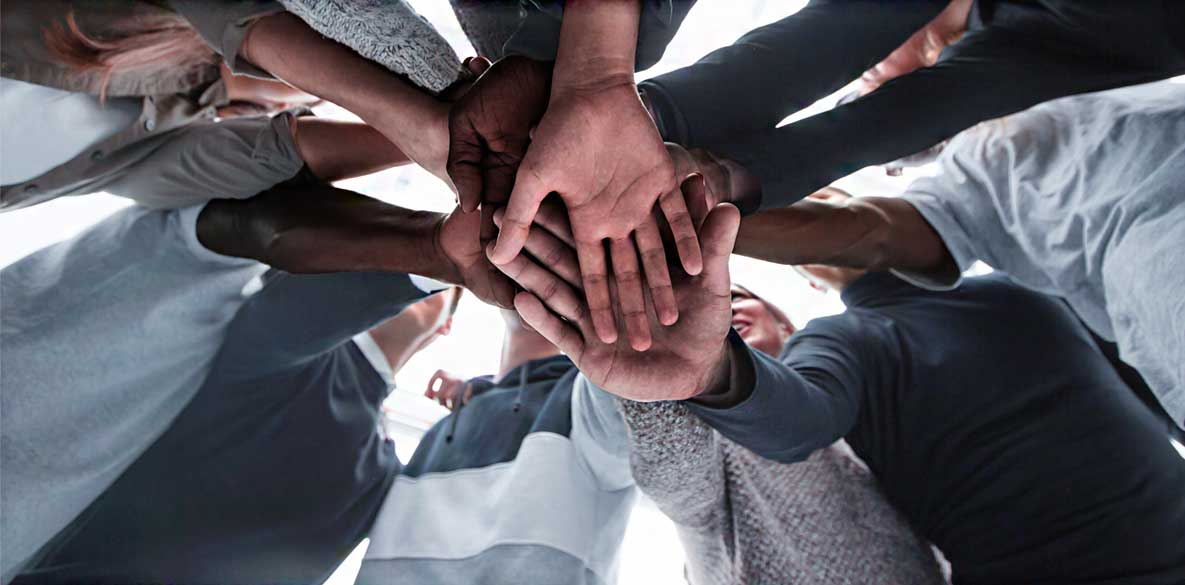 People putting hands in showing teamwork